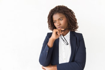 Pensive female manager holding glasses, touching chin. Young African American business woman standing Isolated over white background, looking away.