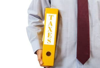 Business taxation. Manager holding a binder folder on white background, text taxes, clipping path