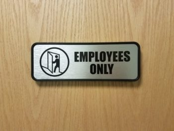 silver and black employees only sign on wood door